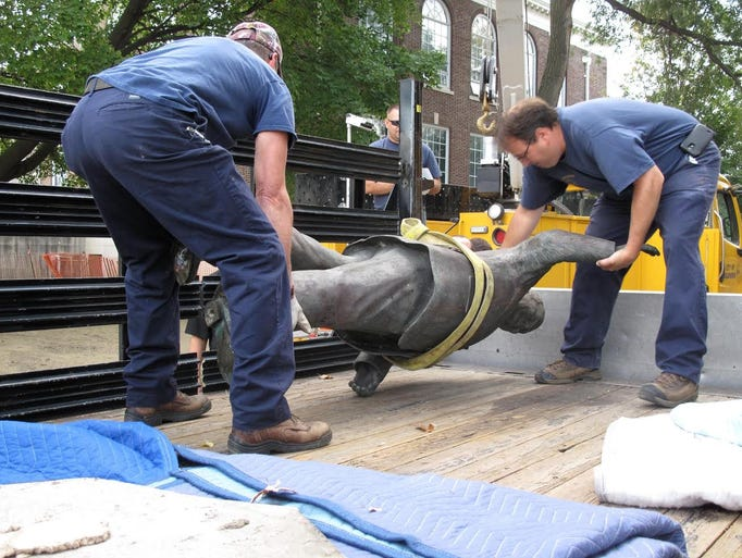 Workers take down the statue of former Mayor Orville