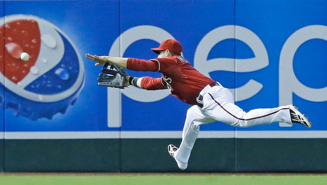 Diamondbacks left fielder Ender Inciarte (5) dives for a ball hit by San Francisco Giants left fielder Tyler Colvin (10) in the 5th inning of  their MLB game Sunday, June 22, 2014, in Phoenix, Ariz.  Colvin was out at third on the play.