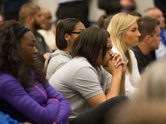 Members of the University of Delaware women's basketball team listen as new women's basketball head coach Natasha Adair is introduced.