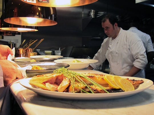 Plates are passed through from the open kitchen at Sails Restaurant, 301 Fifth Ave. S., Naples.