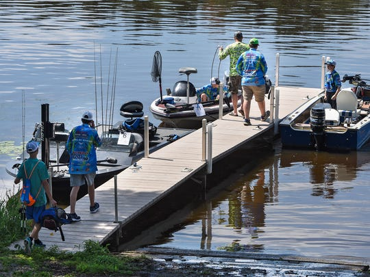 Anglers walk to their boats during a SabreStorm Fishing