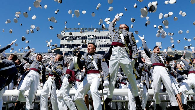 Graduates from the U.S. Military Academy toss their hats into the air after a graduation and commissioning ceremony on Saturday, May 23, 2015, in West Point, N.Y. (AP Photo/Mike Groll)