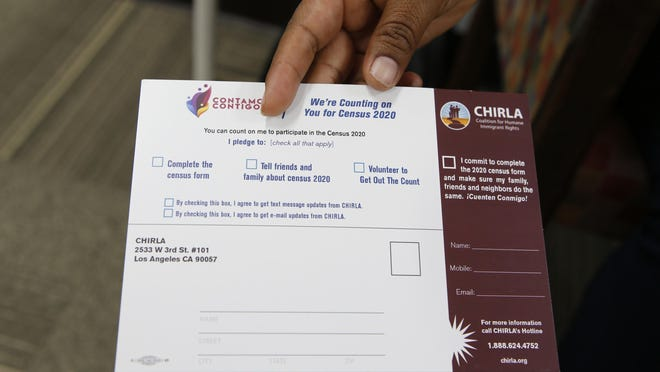 "Coalition for Humane Immigrant Rights, CHIRLA volunteer Angeles Rosales holds up a CHIRLA ""Contamos Contigo,"" ""We Count with You"" census campaign card at the CHIRLA offices in Los Angeles."