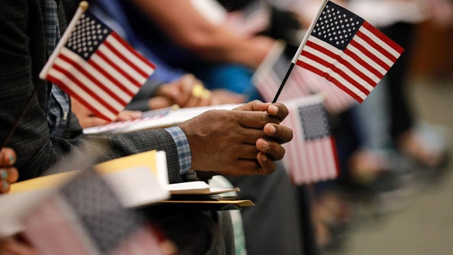 FILE -- Immigrants hold on to American flags ahead of their naturalization ceremony in Washington, Sept. 10, 2019.