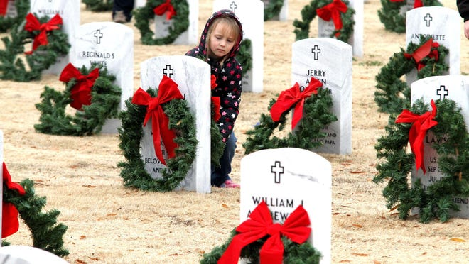 Olivia Proctor is seen placing a wreath during the annual Christmas Honors program at the Fort Smith National Cemetery. The 2020 event this December has been canceled.