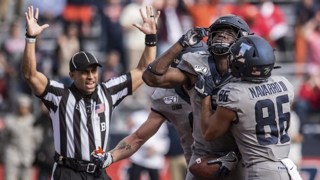 Illinois' Josh Imatorbhebhe, second from right, celebrates with Donny Navarro (86) after scoring a touchdown against Wisconsin, Saturday, Oct.19, 2019, in Champaign. Illinois won 24-21.