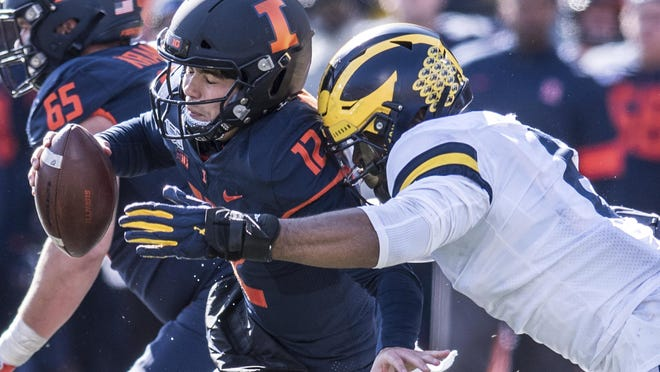 The Big Ten announced Tuesday that it would not hold football games this fall because of concerns about the coronavirus. In this Oct. 12, 2019, photo, Illinois quarterback Matt Robinson (12) is taken down by Michigan's Josh Ache (6) in Champaign.