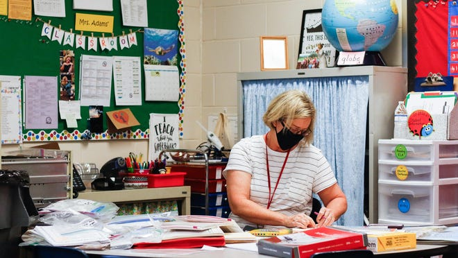 Becky Adams, a first grade teacher at High Shoals Elementary School, organizes her desk in preparation for the upcoming school year in Bishop, Ga., on Friday, July 24, 2020.