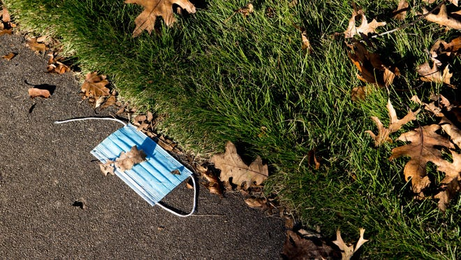 A discarded mask lies on a sidewalk along Milledge Avenue in Athens. The latest state numbers show COVID-19 on the rise in Clarke County.