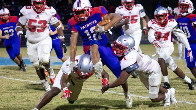 Oglethorpe's Quentin Willis (12) steps over defenders for extra yards during a game between the Oglethorpe County Patriots and the Laney Wildcats at Oglethorpe County High School. After trailing for the majority of the game, Laney pulled ahead in the fourth quarter and won 12-7.