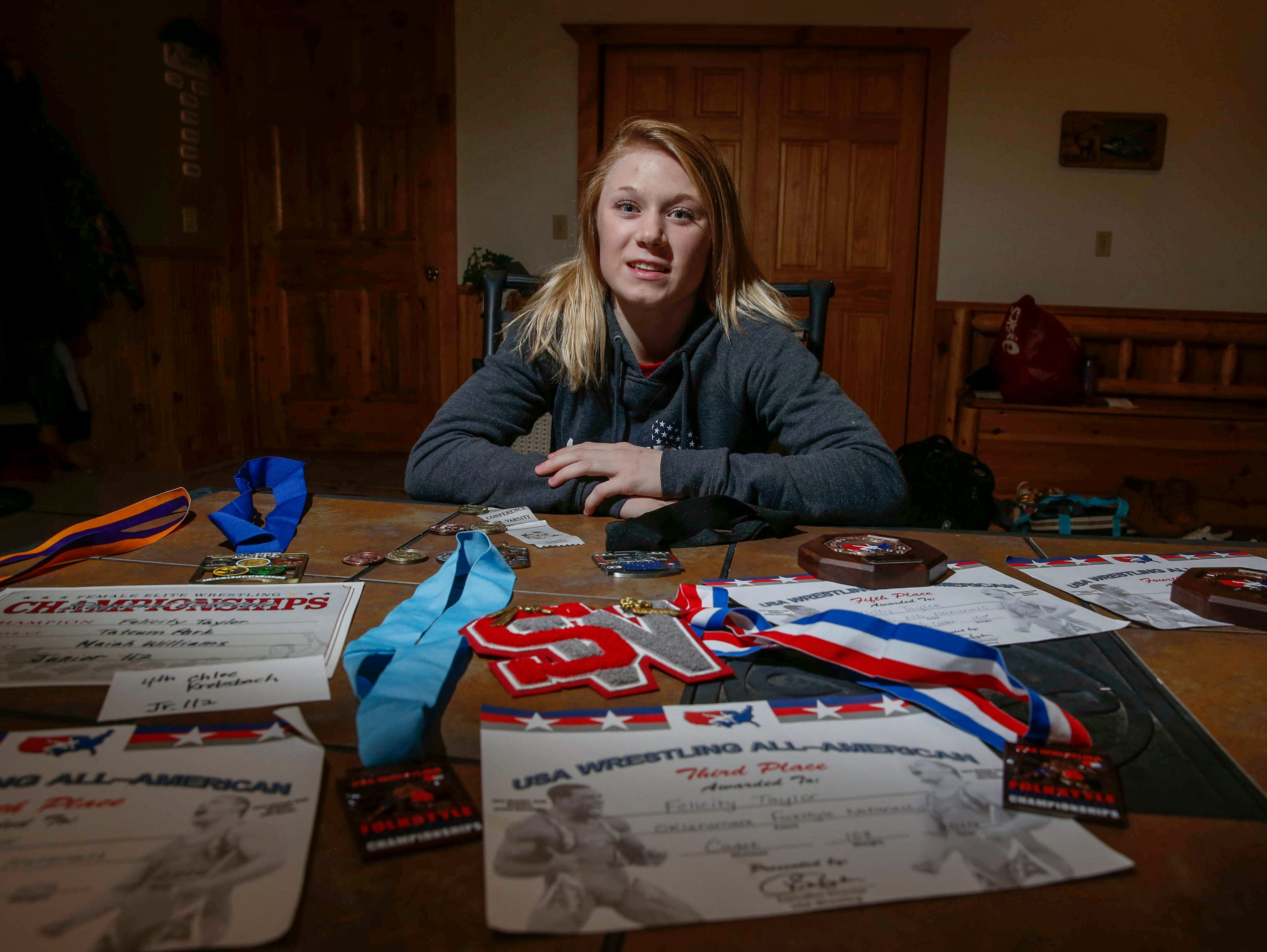 South Winneshiek junior Felicity Taylor poses with some of her wrestling medals and certificates at her home in Spillville, Iowa, on Tuesday, Jan. 31, 2017.