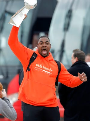 Kansas City Chiefs defensive tackle Chris Jones reacts as he holds up the Vince Lombardi Trophy, as he and his teammates return home a day after winning the NFL Super Bowl 54
