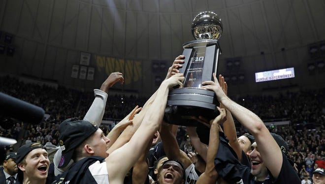 Members of the Purdue basketball team hold up the championship trophy after defeating Indiana 86-75 in an NCAA college basketball game Tuesday, Feb. 28, 2017, in West Lafayette, Ind. Purdue won a share of the Big Ten Conference regular season championship with the win.