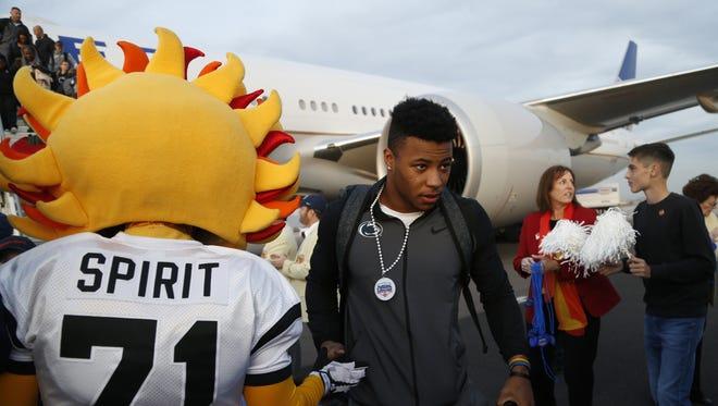 Penn State's Saquon Barkley high-fives Spirit, the Fiesta Bowl mascot, at Phoenix Sky Harbor International Airport on December 23, 2017 in Phoenix, Ariz.