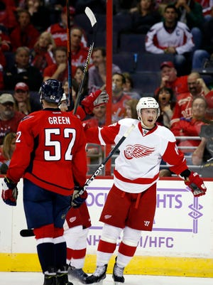 Detroit Red Wings center Gustav Nyquist (14), from Sweden, celebrates his goal as Washington Capitals defenseman Mike Green (52) watches, in the second period of an NHL hockey game, Wednesday, Oct. 29, 2014, in Washington.