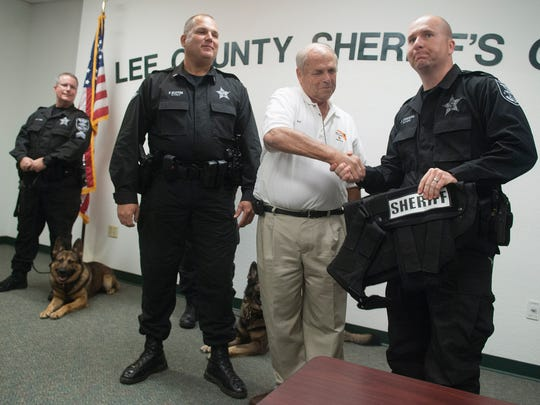 Deputy Jamie Thorpe receives his dog's new ballistic vest from Ray Hubbert. Lee County Sheriff's Office Lt. Frank Glover, head of the K-9 unit, is at left.,