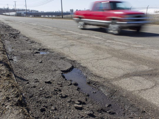 A motorist travels Battle Creek's Raymond Road in March 2015, prior to recent repairs.