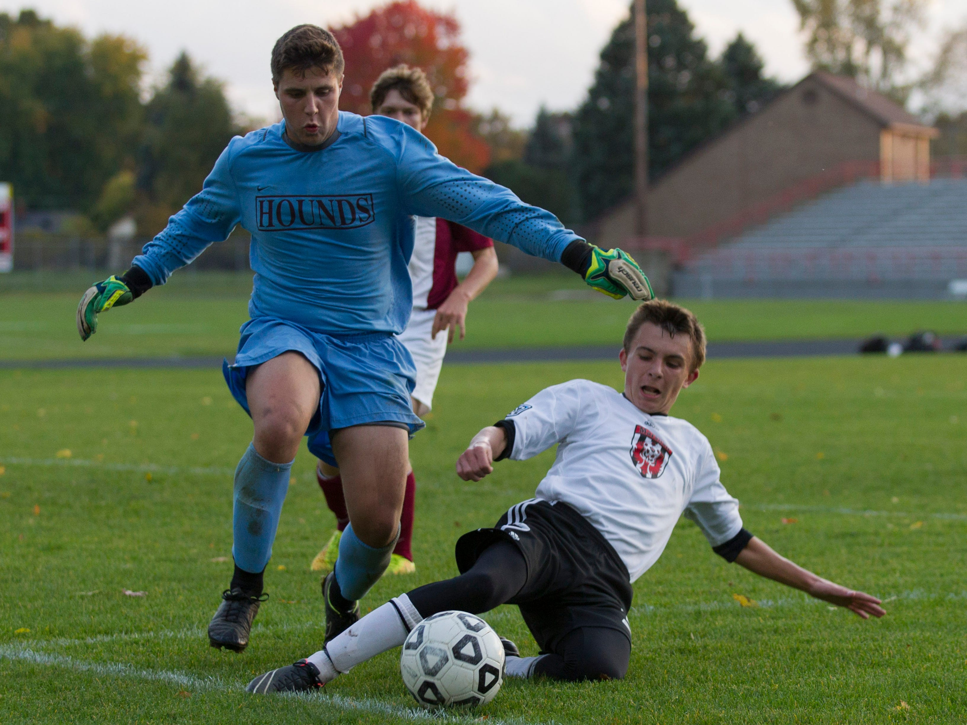 Cody Clapper of Marshall slides in an attempt to keep possession from Eaton Rapids goalkeeper, Jacob Disbro.