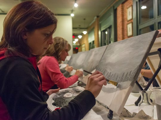 Rachel Banaszak works on her painting at the Wine and Canvas event at Clara's on the River.