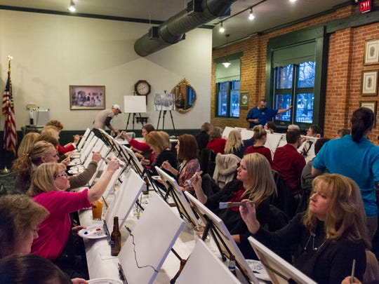 Painters fill a room at Clara's on the River for a Wine and Canvas event.