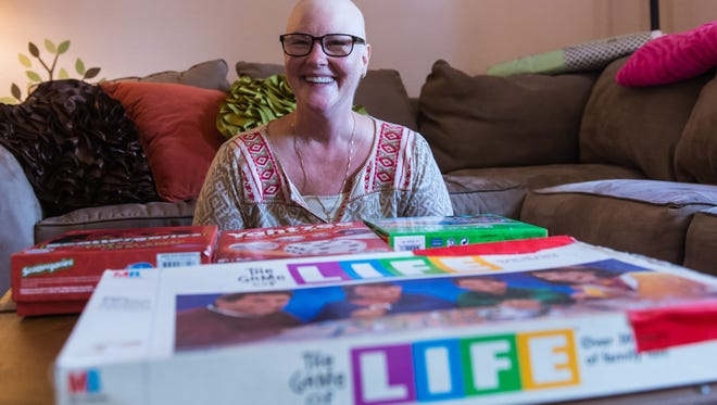"""Lisa Welling sits with a collection of """"brain games"""" she played with her son Louie during chemotherapy at her home in Millville."""