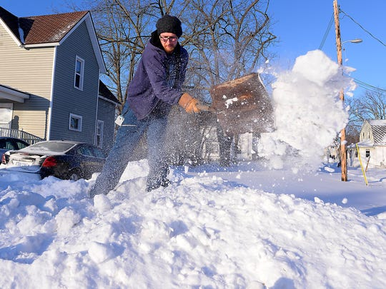 Chad Sibbald of Lansing shovels out a huge pile of drifted and plowed snow near his driveway off Martin Luther King Jr. Boulevard in Lansing on Monday.