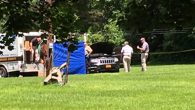 This photo made available by WSLS shows law enforcement surrounding a car that is believed to contain the bodies of a father and child in Raphine, Va., Wednesday, June 6, 2018. Suffolk County police said they are awaiting confirmation that the bodies found in a vehicle in Rockbridge County, Va., are Jovani Ligurgo and his father, John.