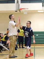 Steve Paul, coach of The Bancroft School's Special Olympics team, plays basketball with student Daniel Menchel.