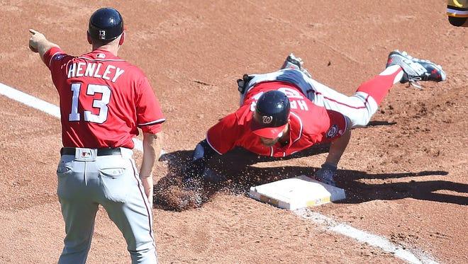 Bryce Harper hurts his thumb sliding into third base on Sunday.