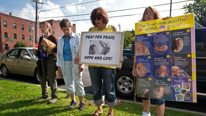 Anti-abortion demonstrators Amy Cochran of Montgomery Center, from left, Sharon Winzler of South Burlington, Rita Mantone of Underhill and Sharon Iszak of Fairfax gather outside Planned Parenthood in Burlington on Wednesday.
