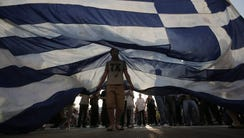 Protesters hold a giant a Greek flag during a rally