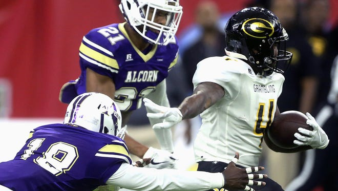 Grambling State's Martez Carter (4) is tackled by Alcorn State's Leishaun Ealey (18) and Jayron Harness (21) during the first quarter of the SWAC Championship on Saturday.