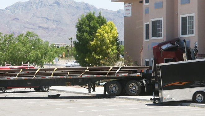 A tractor-trailer rig is shown crashed into the side of a hotel along South Desert Boulevard in West El Paso.