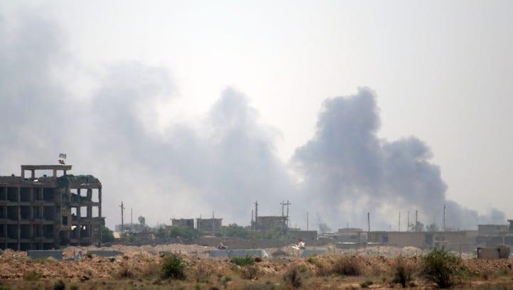 Smoke rises from buildings in Fallujah as members of