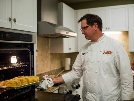 Jude Tauzin, corporate chef for Tony Chachere's Cajun Foods, removes biscuits from an oven in his company kitchen in Opelousas, La., Monday, March 23, 2015.