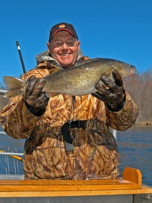 Ron Bruch measures a walleye while working on the Wolf River in April 2009.