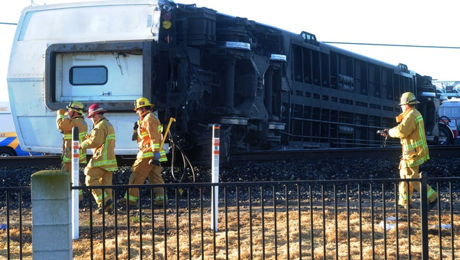 Firefighters inspect the aftermath of the Feb. 24, 2015 deadly Metrolink collision in Oxnard between a commuter train and a vehicle left on the tracks.