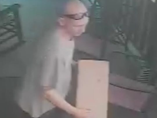 Image from a security camera showing a man stealing a package off a front porch in Easley.