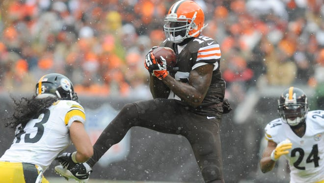 Cleveland Browns wide receiver Josh Gordon  makes a catch as Pittsburgh Steelers strong safety Troy Polamalu  and Pittsburgh Steelers cornerback Ike Taylor defend during the second quarter at FirstEnergy Stadium.