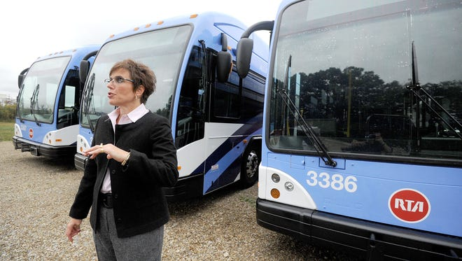 Natalie Beckert, owner of Applied Graphics Ltd, stands in front of three completed bus destined for the RTA system in Cleveland.