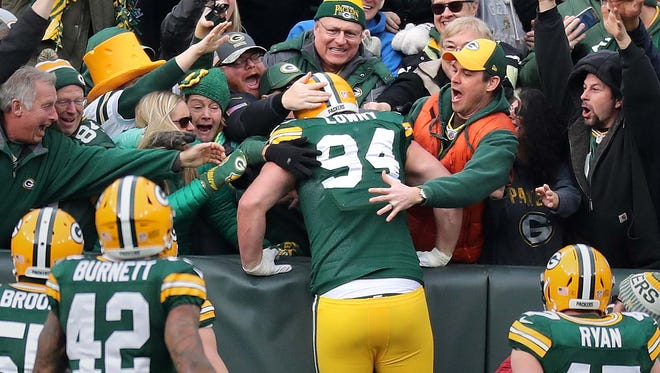 Green Bay Packers defensive end Dean Lowry (94) does a Lambeau leap after scoring a touchdown against the Tampa Bay Buccaneers on Dec. 3, 2017, at Lambeau Field.