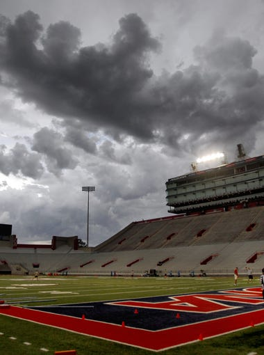 A handful of officials gather in the north end zone as the Wildcats wait out a slow moving storm cell and lightning, delaying the start of the third night of practice for more than an hour at Arizona Stadium, Friday August 7, 2015, Tucson, Ariz. Kelly Presnell / Arizona Daily Star