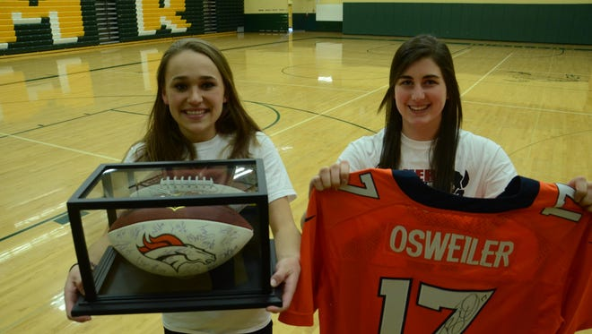 Erynn Murphy, left, and Courtney Schroeder, members of the Health Occupation Students of America chapter at C.M. Russell High School, hold up a football signed by the entire Broncos football team as well as an autographed Brock Osweiler jersey that will be auctioned off during crosstown basketball next week to raise money for a Great Falls boy fighting sickle cell disease.