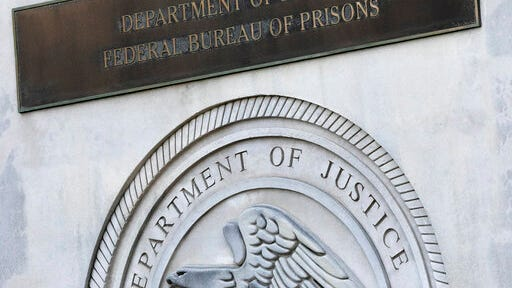 A sign for the Department of Justice Federal Bureau of Prisons is displayed at the Metropolitan Detention Center, Monday, July 6, 2020, in the Brooklyn borough of New York. Jeffrey Epstein's longtime confidante Ghislaine Maxwell has been transferred to New York to face charges she recruited women and girls for him to sexually abuse. The Bureau of Prisons confirmed that Maxwell was transferred Monday and is currently being held at the MDC.