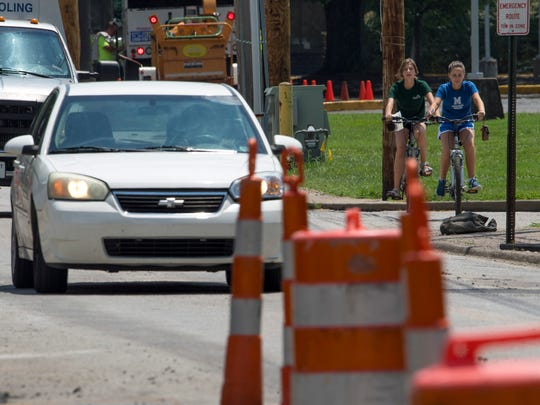 Presley and Paige Gander, 14-year-old twin sisters, make their way up Weinbach Avenue while dodging orange cones and evading loose gravel and rocks Monday afternoon. Construction continues on the project and most likely won't come to fruition until next summer.