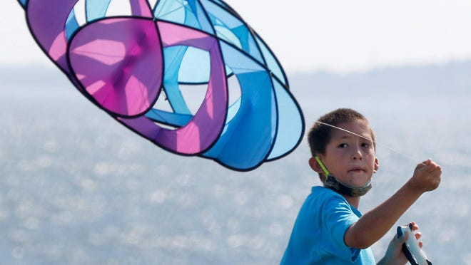Taylor Harrington tries to coax the ocean breeze at Beavertail Park on Jamestown to lift the geometric kite he was flying with on Sunday afternoon.