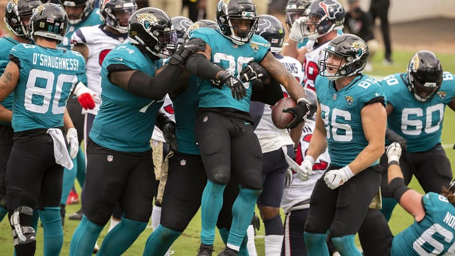 Jacksonville Jaguars players celebrate after running back James Robinson, center, scored a touchdown against the Houston Texans during the first half Sunday, Nov. 8, 2020, in Jacksonville, Fla