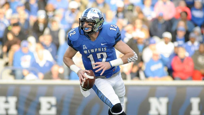 Memphis Tigers quarterback Paxton Lynch (12) runs with the ball against the Connecticut Huskies during the game at Liberty Bowl Memorial Stadium.