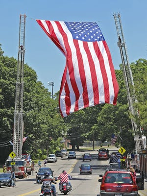 "Quincy was forced to cancel its annual Flag Day parade -- this would have been its 69th year -- due to the coronavirus pandemic. Rather than see the tradition fall to the wayside, the Flag Day Committee held a ""drive under the flag"" event at Merrymount Parkway that gave the city an opportunity to make use of its 30-by-50-foot American flag on Sunday, June 14."
