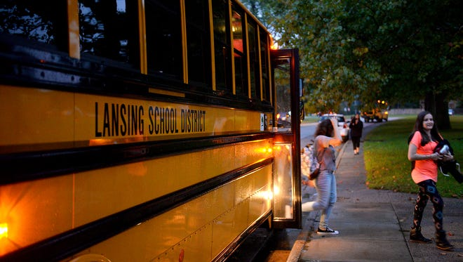 Students file off a Lansing School District school bus Tuesday, September 8, 2015, before the start of the first day of school at Sexton High School.